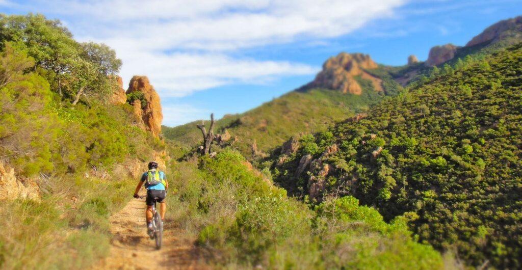 Uomo in bici in mezzo a vegetazione mediterranea e rocce rosse