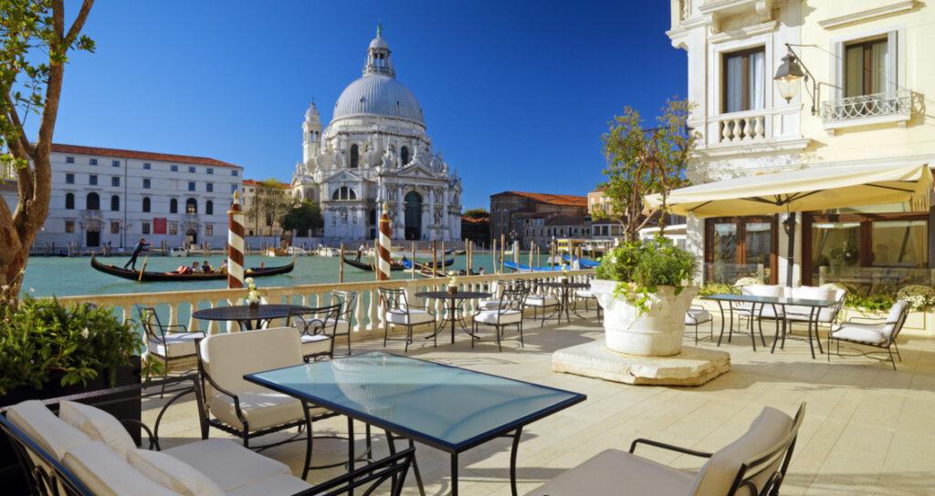 L'immagine rappresenta una terrazza sui canali veneziani! Location suggestiva che vede dei tavolini affacciati sulla laguna con una chiesa e palazzi storici sullo sfondo.