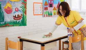 bidella che pulisce un banco a scuola