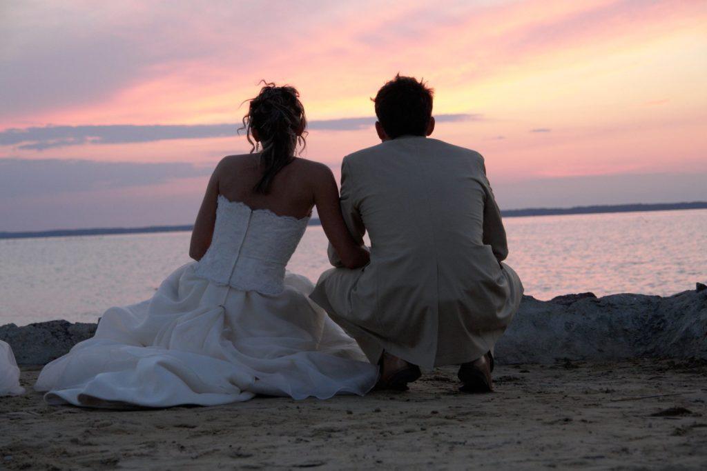 coppia di novelli sposi in spiaggia per un vaggio di nozze sostenibile